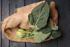 与绿色的撇蓝圆白菜在一金属片离开在老葡萄酒板木背景  免版税库存图片