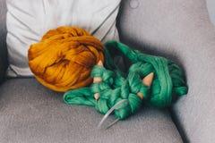 与绿色的橙色美利奴绵羊的羊毛球编织了毯子 免版税库存图片
