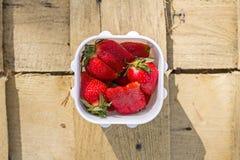 与绿色的甜水多的成熟巨大的草莓莓果在白色塑胶容器离开在木背景在太阳光下 库存照片