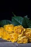 与黄色的静物画凋枯了在黑背景的玫瑰 免版税图库摄影