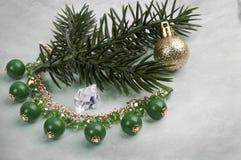 与绿色石头的项链在一棵圣诞树的分支与一个球的在抽象背景 图库摄影
