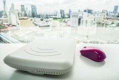 与紫色老鼠的白色访问接入点在办公桌上 库存图片