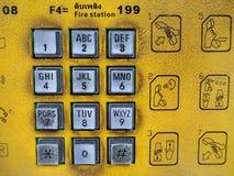 与黄色背景标志指示的肮脏的公用电话银键盘 免版税库存照片