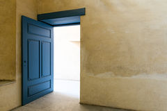 与黄色膏药墙壁的蓝色木葡萄酒门 库存照片