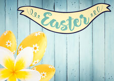 与黄色花和鸡蛋的复活节横幅反对蓝色木盘区 皇族释放例证