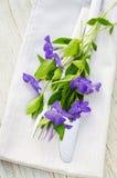 与紫色花的欢乐表设置 库存图片