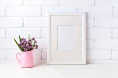 与紫色花的白色框架大模型在桃红色土气投手 库存照片