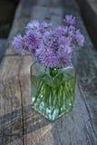 与紫色花的花束香葱在木头的清楚的玻璃 免版税库存照片