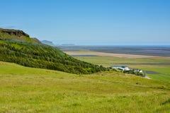 与绿色草甸和房子的农村风景 免版税库存照片