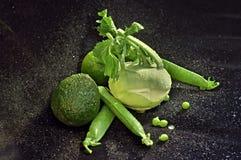与绿色菜的静物画在黑天鹅绒用水滴下 免版税库存图片