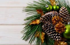 与绿色装饰品、金黄叶子和杉木co的圣诞节花圈 免版税库存图片