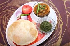 与绿色酸辣调味品和辣椒顶部的Chole bhature 图库摄影