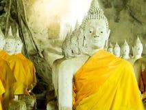 与黄色长袍的倍数思考的菩萨雕塑在c 库存照片