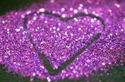 与紫色闪烁的心脏的模糊的抽象背景黑表面上的 免版税库存照片