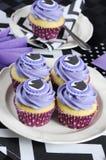 与紫色题材党午餐杯形蛋糕特写镜头的黑白V形臂章 库存图片