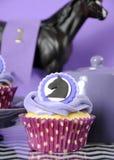 与紫色题材党杯形蛋糕特写镜头的黑白V形臂章 库存照片