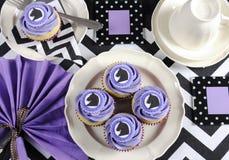 与紫色题材党桌的黑白V形臂章用杯形蛋糕 免版税图库摄影