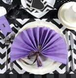 与紫色题材党餐位餐具的黑白V形臂章 免版税库存照片