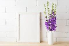 与紫色风轮草花束的白色框架大模型在砖墙附近 免版税图库摄影