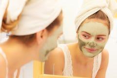 与绿色黏土泥面具的妇女面孔 库存照片