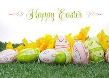 与黄色黄水仙的愉快的复活节五颜六色的桃红色和绿色复活节彩蛋在绿草 免版税库存照片