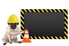 与黄色建筑工人安全帽和空白的警报信号的哈巴狗狗 免版税库存图片