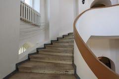 与黄色细长立柱和白色墙壁的螺旋形楼梯 免版税图库摄影