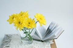 与黄色chrysathemums和书的静物画 免版税库存照片