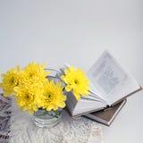 与黄色chrysathemums和书的静物画 免版税图库摄影