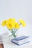 与黄色chrysathemums和书的静物画 免版税库存图片