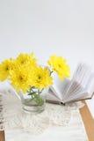 与黄色chrysathemums和书的静物画 库存照片