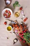 与莴苣叶子和萝卜的混合的地中海蕃茄沙拉在一个木切板 意大利烹调,特写镜头,顶视图 库存图片