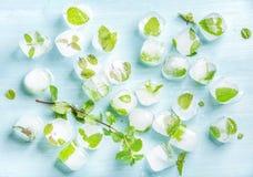 与冻薄荷叶的冰块里面在蓝色绿松石背景 免版税库存图片