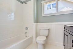 与黑虚荣内阁、洗手间和白色浴盆的蓝色卫生间内部 库存照片