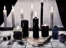 与黑蜡烛和五角星形的神秘的静物画在纸 库存图片