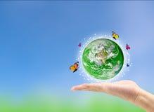 与蝴蝶的地球行星在手中反对 免版税库存图片