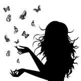 与蝴蝶的妇女剪影在她附近 库存图片