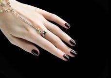 与黑表面无光泽的指甲油的被修剪的钉子 修指甲以黑暗 免版税库存图片