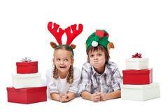 与-被隔绝的礼物和滑稽的帽子的圣诞节孩子 免版税库存图片