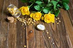 与说谎在一张木桌上的黄色玫瑰的浪漫背景 免版税库存照片