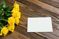 与说谎在一张木桌上的黄色玫瑰的浪漫背景 免版税图库摄影
