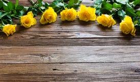 与说谎在一张木桌上的黄色玫瑰的浪漫背景 库存图片