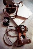 与说谎在地板上的皮革轻的盖子的明亮的photobook 在棕色盒的下两照相机 库存照片