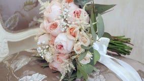 与说谎在椅子的桃红色花的美丽的婚礼花束在屋子里 免版税库存照片