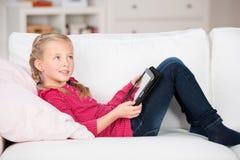 与说谎在沙发的数字式垫的孩子 免版税库存图片