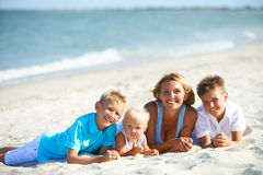 与说谎在海滩的孩子的Happymother 免版税库存照片