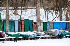 与说谎在冻湖岸的渔夫小船的冬天风景 图库摄影