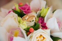 与说谎在bride& x27的金刚石的两只婚姻的金戒指; 白色兰花和桃红色花s花束  库存照片