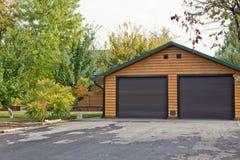 与2辆汽车车库的小原木小屋被修建远离城市在森林 免版税库存图片
