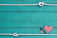 与绳索边界的空白的蓝色标志,红色心脏、铁钥匙和银锁 库存图片